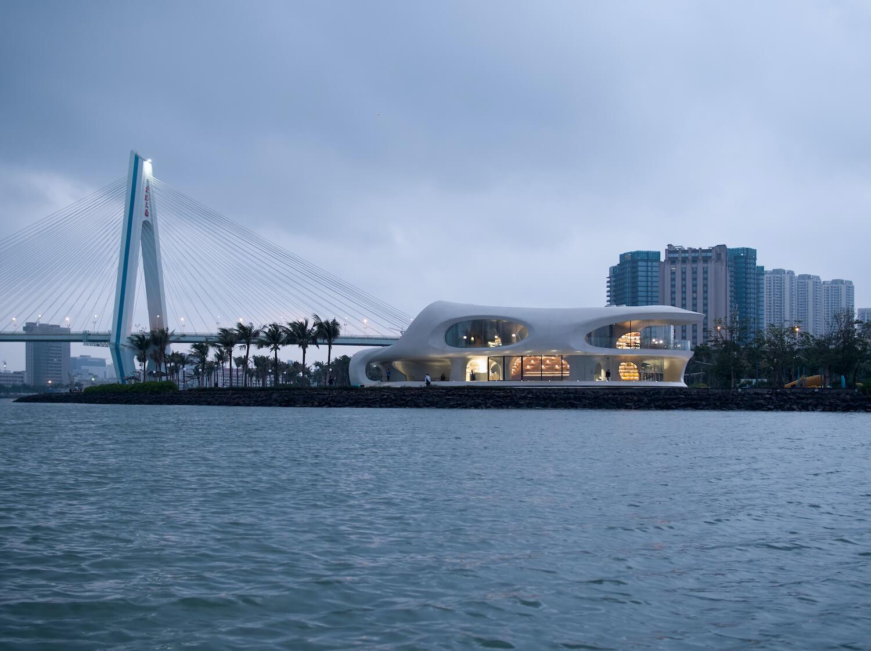 futuristic building in china next to bridge